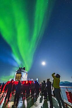 Passengers observing and shooting the Northern Lights from the upper Deck 9 of the ms Trollfjord on the northbound voyage, Oct 16, 2019, north of Tromsø. Illumination is from the waning gibbous Moon in frame at right.