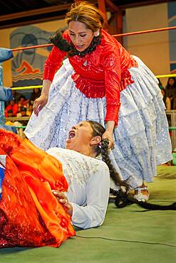 Lucha Libre. Combat between Dina with orange skirt and Benita la Intocable , cholitas females wrestlers ,Sports center La Ceja, El Alto, La Paz, Bolivia
