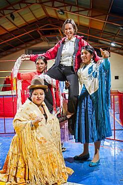 Lucha Libre. After the show. A follower is photographed with cholitas fighters. Down Julieta,  Celia la Simpatica, and Dina with blue dress , cholitas females wrestlers ,Sports center La Ceja, El Alto, La Paz, Bolivia