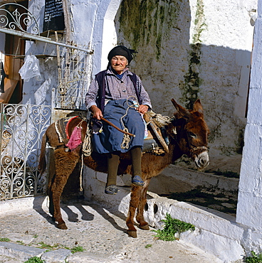 Portrait of an old woman sitting on a donkey in a village in Greece, Europe