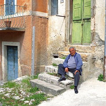 Old man sitting on steps in the old part of the town of Capolaterra, Norcia, Umbria, Italy, Europe