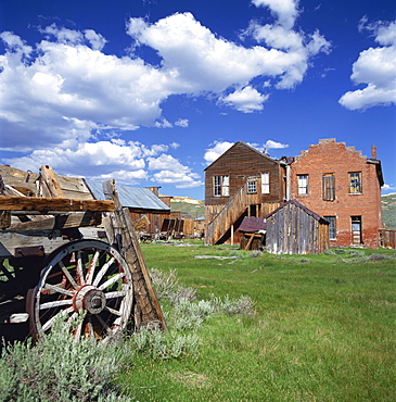 Old farm wagon and derelict wooden and brick houses at Bodie Ghost Town, California, United States of America, North America