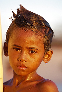 Portrait of a boy with a wet face after learning to surf at Kuta Beach, Bali, Indonesia, Southeast Asia, Asia