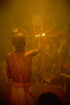 Temple priest before the image of the ten armed warrior goddess Durga, Durga Puja Festival, Varanasi, Uttar Pradesh state, India, Asia