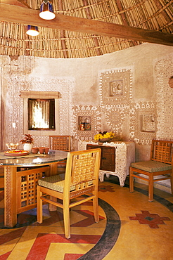 Raised mud reliefs inlaid with mirror on the walls of dining area in modern home in traditional tribal Rabari round mud hut, Bunga style, near Ahmedabad, Gujarat state, India, Asia
