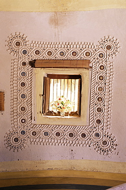 Raised mud reliefs inlaid with mirror on the walls of modern home in traditional tribal Rabari round mud hut, Bunga style, near Ahmedabad, Gujarat state, India, Asia