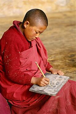 Young Buddhist monk practising writing, Bhutan, Asia