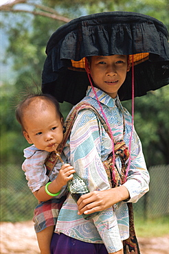 Woman in traditional dress and large black frilled hat, with her baby, in Hong Kong, China, Asia