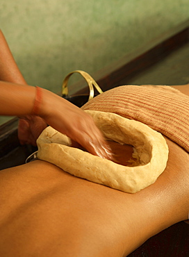 Kathi Vasti Treatment, an Ayurvedic procedure retaining warm medicated oil over the lower back within a border of herbal paste