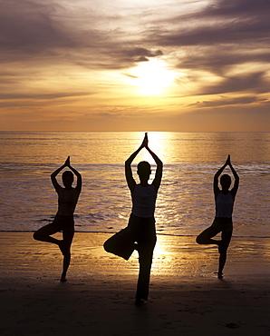 Yoga on the beach at sunset