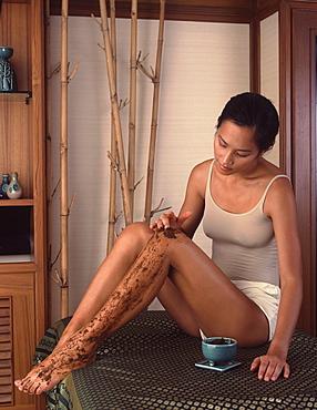 Woman applying a scrub at a spa, Thailand, Southeast Asia, Asia
