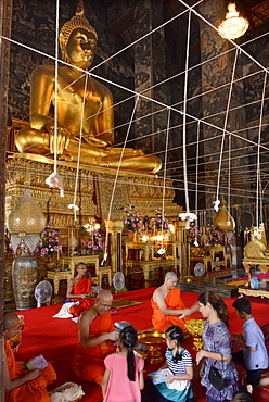Monk blessing people in the main Viharn of Wat Suthat Bangkok, Thailand, Southeast Asia, Asia