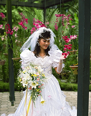 Bride looking at orchids, Asia