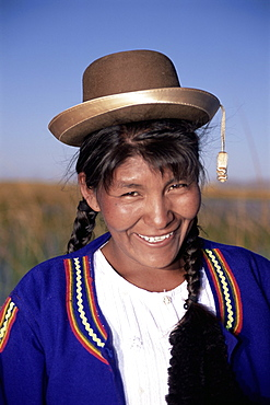 Head and shoulders portrait of a smiling Uros Indian woman, Islas Flotantes, floating islands, Lake Titicaca, Peru, South America