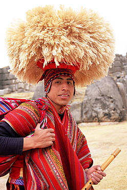 Portrait of a young Peruvian man in traditional dress, with hat and flute, Sacsayhuaman, near Cuzco, Peru, South America