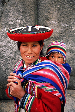 Portrait of a local woman in traditional dress, carrying her baby on her back, in front of Inca ruins, near Cuzco, Peru, South America