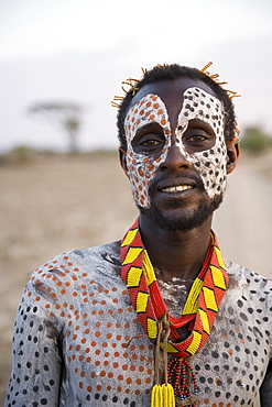 Portrait of a Karo tribesman, with face and body painted with chalk to represent the spotted plumage of the guinea fowl, Omo river, Lower Omo Valley, Ethiopia, Africa