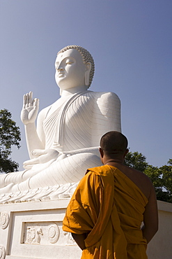 Monk standing in front of the great seated figure of the Buddha, Mihintale, Sri Lanka, Asia