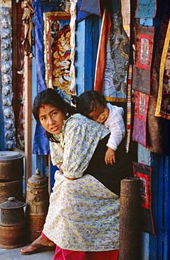 Woman and baby, cloth shopkeeper in temple square, Bodhnath, Kathmandu, Nepal