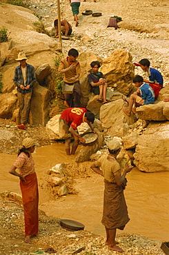 Children sieving and washing small gems from stream below mine, Mogok ruby mines, near Mandalay, Myanmar (Burma), Asia