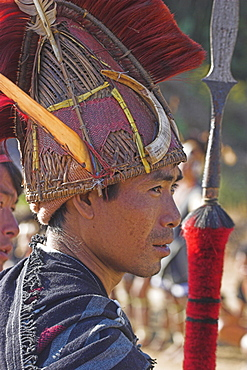 Naga man with spear wearing headdress made of woven cane decorated with wild boar teeth, Mithan horn (wild cow) red dyed goats hair and  hornbill feathers, Naga New Year Festival, Lahe village, Sagaing Division, Myanmar (Burma), Asia