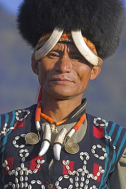 Naga man wearing headdress made of woven cane decorated with wild boar teeth and  bear fur and  wearing a tiger teeth necklace, Naga New Year Festival, Lahe village, Sagaing Division, Myanmar (Burma), Asia