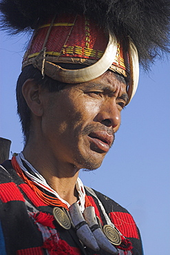 Naga man wearing headdress made of woven cane decorated with wild boar teeth and  bear fur with Tiger claw straps and  wearing tiger teeth necklace, Naga New Year Festival, Lahe village, Sagaing Division, Myanmar (Burma), Asia