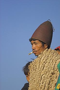 Naga man  wearing cane hat, heirloom blanket and smoking cheroot, Naga New Year Festival, Lahe village, Sagaing Division, Myanmar (Burma), Asia