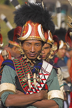 Naga man wearing headdress made of woven cane decorated with wild boar teeth, bear fur, red dyed goats hair with strap of tiger claws also wearing tiger teeth necklace and ivory arm band, Naga New Year Festival, Lahe village, Sagaing Division, Myanmar (Burma), Asia