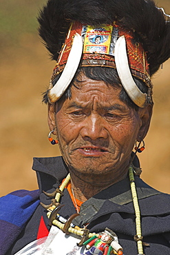 The Naga  (Macham tribe) chief of the village wearing traditional hat made of woven cane decorated with wild boars teeth and bear fur, also bead necklace with tiger teeth, Magyan Village, Sagaing Division, Myanmar (Burma), Asia