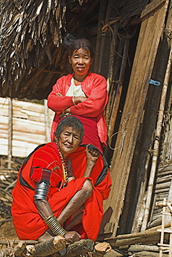 Naga (Macham tribe) ladies outside house, the lady in the foreground has face and leg tattoos, done in childhood so that they are not attractive to men who might steal them from the village, Magyan Village, Sagaing Division, Myanmar (Burma), Asia