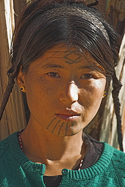 Naga (Macham tribe) girl with face tattoos, done when they are children so that they are not attractive to men who might steal them from their village) carrying wood on her back, Magyan Village, Sagaing Division, Myanmar (Burma), Asia