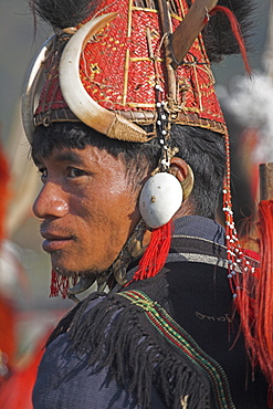 Naga man in headdress of woven cane decorated with wild boar teeth, Mithan horns (wild cow) and bear fur, wearing conch shell ear ornament with a tiger claw chin strap, Naga New Year Festival, Lahe village, Sagaing Division, Myanmar (Burma), Asia