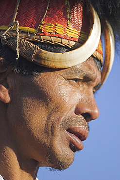 Naga man wearing headdress made of woven cane decorated with wild boar teeth, Mithan horns (wild cow) and bear fur and wearing conch shell ear ornament with a tiger claw, Naga New Year Festival, Lahe village, Sagaing Division, Myanmar (Burma), Asia