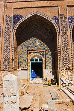 Lady pilgrim in blue burqa sitting in doorway at Sufi shrine of Gazargah, Herat, Herat Province, Afghanistan, Asia