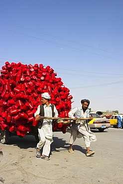 Men pulling wooden cart piled high with red water containers along road, Mazar-I-Sharif, Balkh province, Afghanistan, Asia