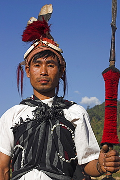 Naga man holding spear and wearing headdress of woven cane decorated with wild boar teeth, bear fur, red dyed goats hair and hornbill feathers, Naga New Year Festival, Lahe village, Sagaing Division, Myanmar (Burma), Asia