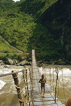 Child crossing bridge, South Beliam Valley, Irian Jaya, Indonesia, Southeast Asia, Asia