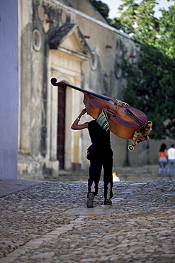 Musician carrying double bass along cobbled street to Plaza Mayor, Trinidad, Cuba, West Indies, Central America