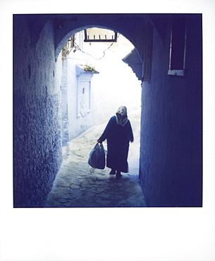 Woman in semi-silhouette walking through archway, Chechaouen, Morocco, North Africa, Africa
