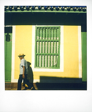 Polaroid of man walking past yellow wall with painted green window grille, Trinidad, Cuba, West Indies, Central America