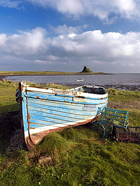 View towards Lindisfarne Castle with old fishing coble and lobster pots in the foreground, Holy Island, Northumberland, England, United Kingdom, Europe