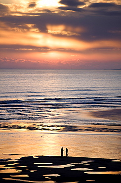 Man and woman in silhouette looking out over North Sea at sunsrise from Alnmouth Beach, near Alnwick, orthumberland, England, United Kingdom, Europe