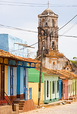 Street scene showing houses painted in bright colours and the ruins of an old church, Trinidad, UNESCO World Heritage Site, Cuba, West Indies, Central America
