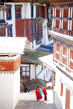 Two Buddhist monks chatting against the imposing backdrop of Trongsa Dzong, Trongsa, Bhutan, Asia