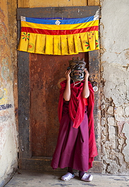 Young Buddhist holding holding carved wooden mask over his face at the Tamshing Phala Choepa Tsechu, near Jakar, Bumthang, Bhutan, Asia