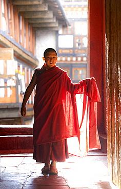 Young Buddhist monk in red robes backlit by evening sunlight at the Jakar Dzong, Jakar, Bumthang, Bhutan, Asia