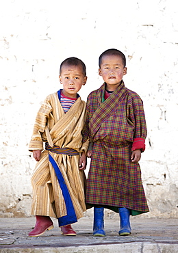 Two boys in front of white wall at Ura Lhakhang, Ura village, near Jakar, Bumthang, Bhutan, Asia