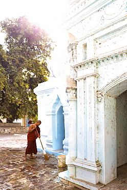 Buddhist monk cleaning paving outside a small temple near the famous U Bein teak bridge, Amarapura, near Mandalay, Myanmar (Burnma), Asia