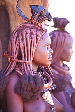 Young Himba woman wearing traditional dress and jewellery and with her skin covered in Otjize, a mixture of butterfat and ochre, Kunene Region, formerly Kaokoland, Namibia